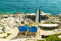 Sunbeds och paraplyer (slags solskydd) på stranden i den Korfu ön, Grekland Arkivfoto