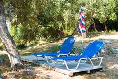 Sunbeds och paraplyer (slags solskydd) på stranden i den Korfu ön, Grekland Royaltyfri Foto