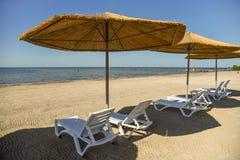 Sunbeds och rottingparaplyer på en sandig strand arkivfoton