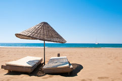 Sunbeds och rottingslags solskydd på den sandiga sjösidan. Arkivfoto