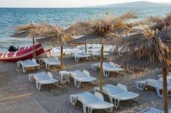Sunbeds och rottingslags solskydd på den sandiga stranden Royaltyfri Bild