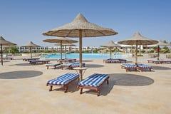Sunbeds och slags solskydd vid ett tropiskt hotell tillgriper simbassängen Royaltyfri Bild