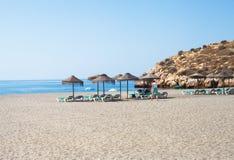 Sunbeds och sugrörparaplyer på stranden Royaltyfria Bilder