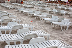Sunbeds in the off-season. Empty chairs on sandy beach Royalty Free Stock Photos