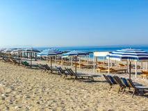 Sunbeds onder blauwe paraplu's op het lege kiezelsteenstrand stock fotografie