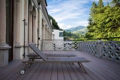 Sunbeds på balkongen med den härliga sikten av bergen på t Arkivfoto