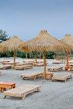 Sunbeds på den tropiska stranden Arkivfoto
