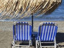 Sunbeds på den Vlichada stranden, Santorini, Grekland arkivfoto