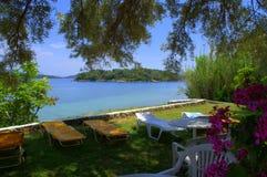 Sunbeds på gräsmatta för kust för Ionian hav Royaltyfri Bild