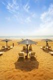 Sunbeds på sandig strand Arkivbild