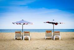 Sunbeds på stranden och den blåa himlen Arkivfoto