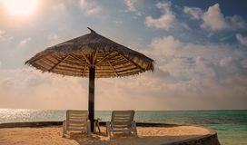Sunbeds and palm tree umbrellas on a background of a beautiful sunset Royalty Free Stock Photography