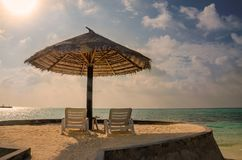 Sunbeds and palm tree umbrellas on a background of a beautiful sunset over the Indian Ocean, Maldives stock image