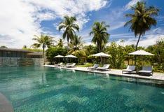 Sunbeds, parapluies et piscine Photographie stock
