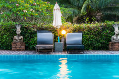 Sunbeds and parasol on wooden deck nearby swimming pool Stock Image