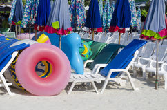 Sunbeds, parasols και λαστιχένια δαχτυλίδια στην παραλία Στοκ Φωτογραφία
