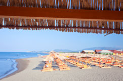 Sunbeds and parasols on the beach , Defocused Stock Image