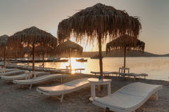 Sunbeds with parasols at Mirabello Bay on Crete Stock Photos