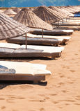 Sunbeds and parasols on sandy beach. Royalty Free Stock Photography