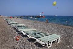 Sunbeds on pebbled beach of Mediterranean resort. Royalty Free Stock Photos