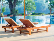 Sunbeds placed beside swimming pool Stock Photography