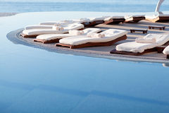 Sunbeds by the pool. Empty sunbeds by the beautiful resort pool Stock Image