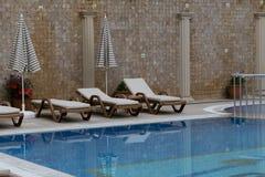 Sunbeds por la piscina al aire libre fotografía de archivo