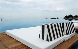 Sunbeds por la piscina con vistas al mar Fotografía de archivo