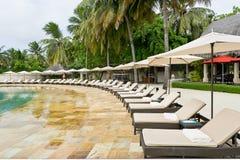 Sunbeds près de la piscine Photographie stock