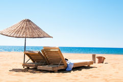 Sunbeds and rattan parasols on sandy seaside. Royalty Free Stock Photography