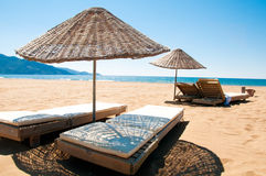 Sunbeds and rattan parasols on sandy seaside Royalty Free Stock Images