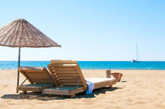Sunbeds and rattan parasols on sandy seaside. Stock Image