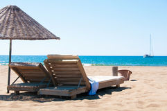 Sunbeds and rattan parasols on sandy seaside Royalty Free Stock Photo