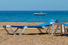 Sunbeds on rocky beach and parasailing speed boat waiting for customers Stock Image