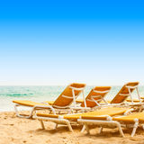 Sunbeds on the sandy beach Stock Photography