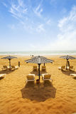 Sunbeds on sandy beach Stock Photography