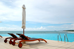 Sunbeds at the sea view swimming pool Stock Images