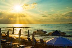 Sunbeds and straw umbrellas on sunset European beach. Crete shore, sun`s rays cut through the clouds royalty free stock photo
