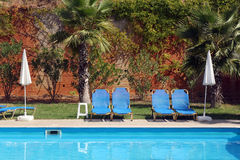 Sunbeds and sun umbrellas by the swimming pool Stock Photos