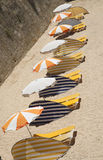 Sunbeds and sunshades on a beach Stock Images