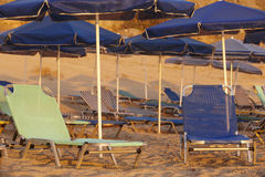 Sunbeds and sunshades in a mediterranean beach. Crete Royalty Free Stock Photos
