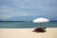 Sunbeds sur une plage lointaine Image stock
