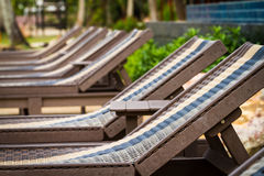 Sunbeds beside swimming pool Stock Photo