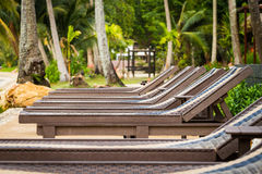 Sunbeds beside swimming pool Stock Photography