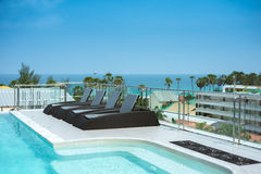 Sunbeds at swimming pool of luxury hotel Royalty Free Stock Photo