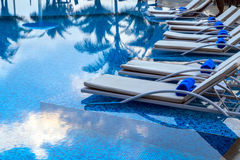 Sunbeds beside swimming pool Royalty Free Stock Photography
