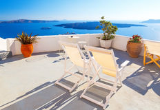 Sunbeds on the terrace of hotel. Santorini island, Greece. Beautiful summer landscape with sea view Stock Photos