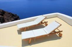Sunbeds on the terrace on Santorini island, Greece. Stock Images