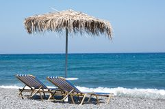 Sunbeds and umbrella. On the beach Stock Image