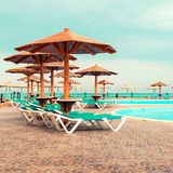 Sunbeds and umbrella around the pool on sunny day Royalty Free Stock Photography